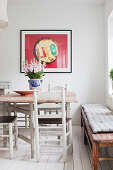 Dining table and country-house chairs below framed poster