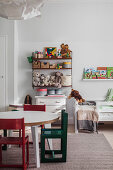 Table, chairs, cabinet and toys on shelves in child's bedroom