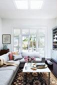 Ecksofa und Couchtisch mit Marmorplatte im Wohnzimmer, im Hintergrund Terrassentür