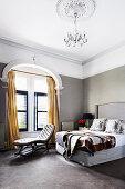 Doppelbett mit hohem Kopfende und Chaiselongue vor Fenster im Schlafzimmer