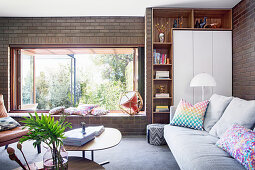 Sofa in front of shelf and cupboard and coffee table in living room with open window and wide windowsill