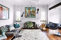 Upholstered sofa, designer chair and fireplace in the living room, modern art on the wall