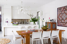White fitted kitchen with island and wooden dining table with white chairs