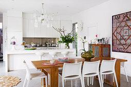 weiße Einbauküche mit Kücheninsel und Esstisch aus Holz mit weißen Stühlen
