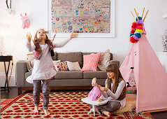Girls playing on patterned carpet in front of pink teepee in living room