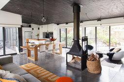 Lichtdurchfluteter Wohnraum mit Küche, Essbereich und Lounge, Kamin in der Mitte