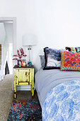 Elegant lamp on bedside table next to bed with colorful pillows