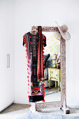 Standing mirror with wooden frame, caftan and hat hung over the mirror