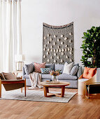 Graues Polstersofa mit Kissen, Couchtisch, Sessel und Stuhl als Aufbewahrungsmöbel