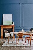 Esstisch mit Holzstühlen vor grauer Kassettenwand und Kamin