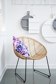 Colourful cushion on rattan easy chair below chopping boards hung from row of hooks