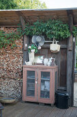 Crockery in antique cabinet with vase of geraniums on top
