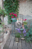Vintage-style arrangement of potted plants, candles and wreath on terrace