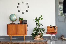 Globe on sideboard below circular arrangement of black-and-white photos on wall, houseplants and wooden crate on stool