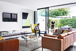 Family in modern living room with window front to garden
