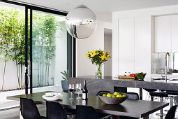 Dining table in front of the modern open kitchen with patio door