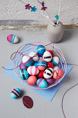 Basket of Easter eggs and branches decorated with paper flowers in vase