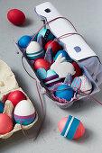 Verzierte Ostereier und Osterhase im Eierkarton