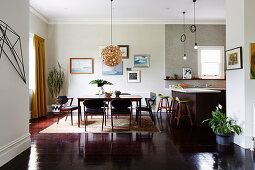 Open living room with dark floor and dining table in front of the kitchen