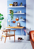 Desk on blue wall strip with wall shelves