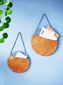 Round leather and felt storage bags on a light blue wall