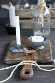 Candles in metal holders on chopping board