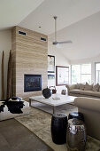 Beige sofa set, fireplace, coffee table and side tables in bright living room