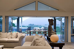 Elegant sofa set and Buddha statue on console table in lounge in front of terrace with view of landscape