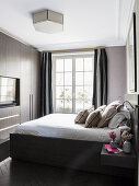 Classic bedroom in dark shades with fitted cupboards
