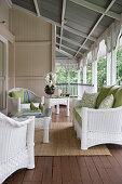 White rattan furniture with green cushions on veranda