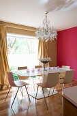 Designer dining table and chairs below chandelier in dining room with hot-pink wall
