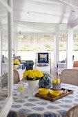 Blick durchs offene Fenster auf die Veranda mit Deko in Gelb und Blau