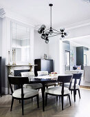 Upholstered chairs around oval dining table in elegant gray dining room
