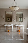 Pair of 20th century basins in bathroom with grey marbled floors, wall mirrors and silk lampshade