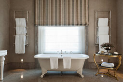 Free standing claw foot bath in bathroom with grey marble floors and wall hung towel warmers
