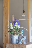 Driftwood arranged in zinc bucket and decorated with summer flowers