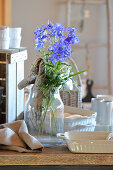 Gnarled root and delphiniums in glass vase