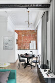 Round dining table with bistro chairs and kitchen with brick wall in small apartment