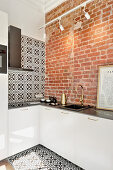 Kitchen with brick wall and black-and-white tiles on wall and floor in small apartment