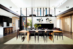 Long dining table with chairs in a high, open living room