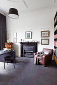 Leather armchairs next to fireplace in study