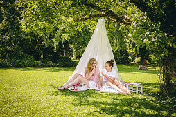 Two friends sitting under DIY canopy in garden