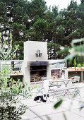 Gartentisch mit Bank und Stühlen vor Grill auf der Terrasse