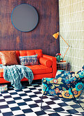 Red leather couch with pillows and plaid, side table and chair with floral cover on checkered pattern floor