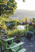 Small terrace with Adirondack armchair at the garden pond