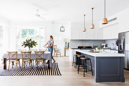 Open kitchen with kitchen island, woman at table in background