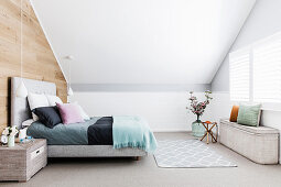 Double bed with pillows, pendant lamp, bedside table and chest in the attic bedroom
