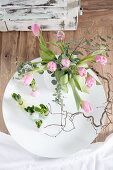 Spring arrangement of tulips in spherical vase and hyacinths with waxed bulbs