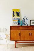 Retro sideboard with poster and vases, chair next to it