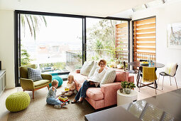 Children sieling in front of a sofa on a carpet in the living room with a sliding glass door to the terrace